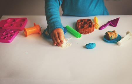Child playing with clay molding shapes Stock Photo