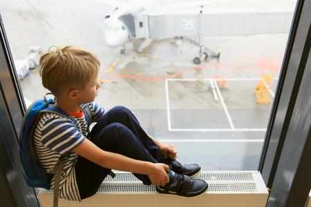 飛行機を見ている小さな男の子が空港で旅行