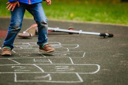 kleine jongen hinkelspel spelen op de speelplaats Stockfoto