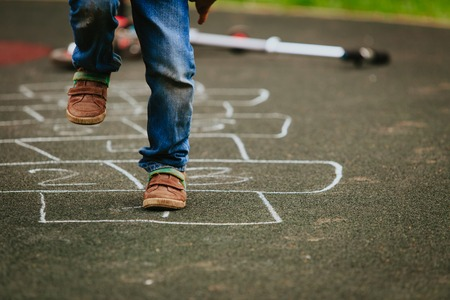 little boy playing hopscotch on playground Imagens