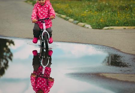 little girl riding bike in water after rain, kids outdoor