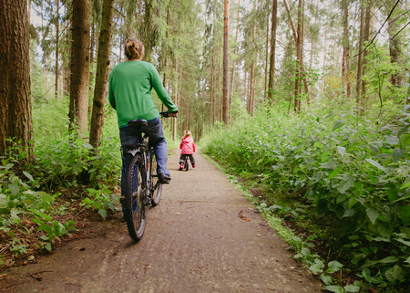 mother and little daughter riding bikes in nature, active family