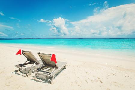 ビーチのクリスマス-海でサンタの帽子が付いているラウンジの椅子 写真素材