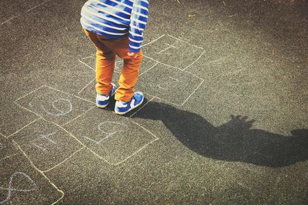 little boy playing hopscotch on playground Stock Photo