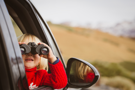 little girl looking through binoculars travel by car in mountains