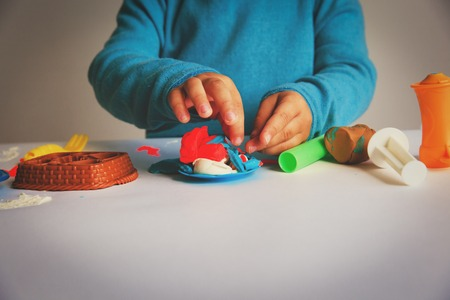 Child playing with clay molding shapes Фото со стока