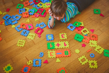 little boy playing with puzzle, education concept Banco de Imagens
