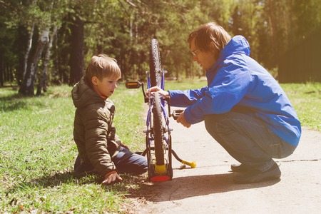 father and son fixing bike in nature Stock Photo