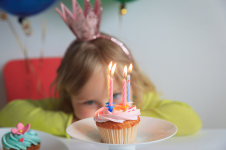 little girl making wish at birthday party