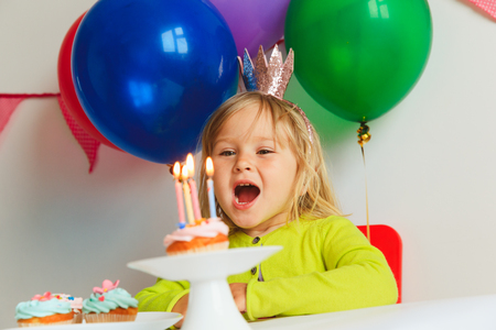 happy little girl make wish blow candles at birthday party