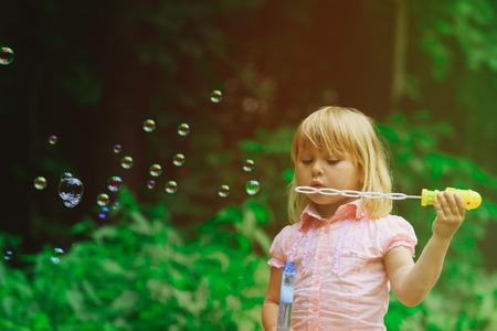 Mignonne petite fille soufflant des bulles de savon Banque d'images - 86584442