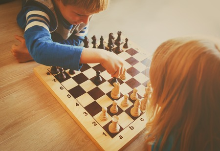little boy and girl play chess Stock Photo