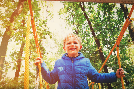 happy little boy climbing on outdoor playground