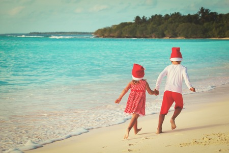 little boy and girl in santa hats having fun on tropical beach at christmas
