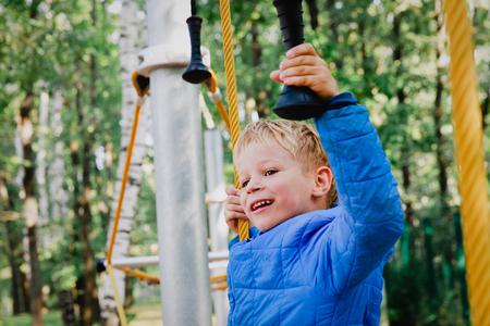 happy little boy climbing on outdoor playground
