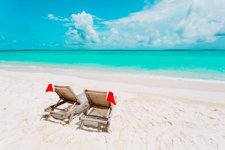 海でサンタの帽子を持つビーチチェアラウンジでのクリスマス