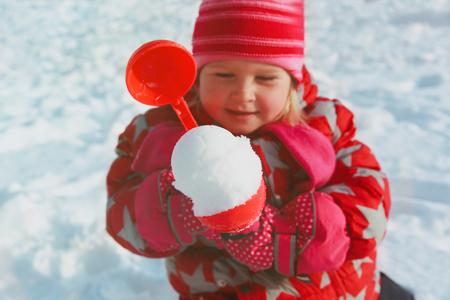 little girl making snowball in winter nature Banco de Imagens