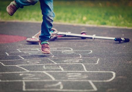 Petit garçon jouant à la marelle sur terrain de jeu Banque d'images - 87225263
