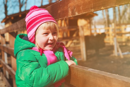 happy little girl looking at animals in farm or zoo Stock Photo