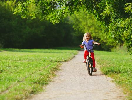 little girl riding bike in nature