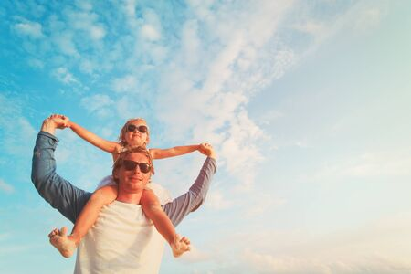 cute guy: father and happy little daughter play at sky