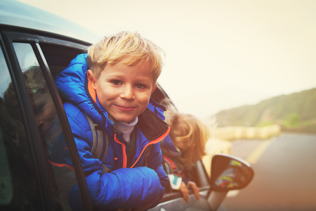 cute guy: happy little boy and girl travel by car Stock Photo