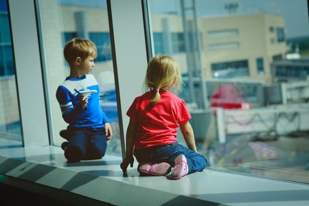 cute guy: little boy and girl waiting plane in airport