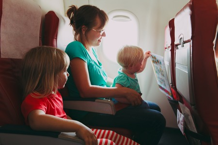 cute guy: family travel by plane- mother wtih two kids in flight