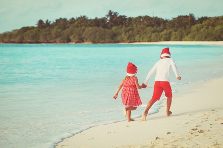 christmas on beach- happy kids with santa hats play at sea