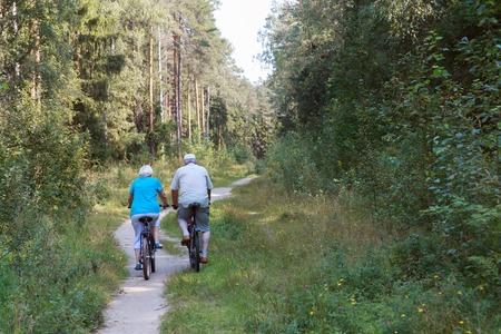 active senior couple riding bikes in nature