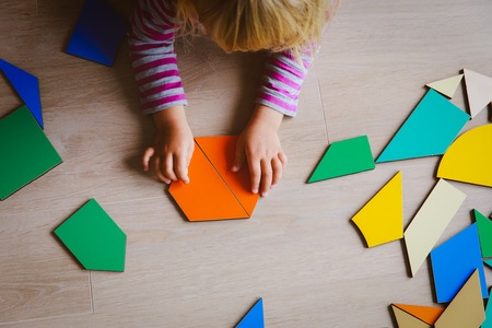 little girl playing with puzzle in school or daycare Stock Photo