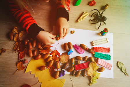 Halloween preparation. Little girl making crafts from clay and natural materials
