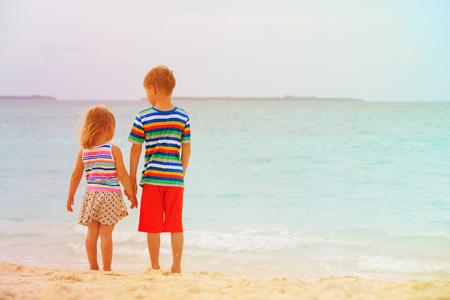 小さな男の子と幼児女の子繋いでビーチの上を歩く 写真素材 - 88283167
