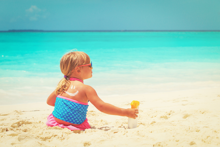 sun protection at beach- little girl applying sunblock cream on shoulder