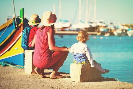 몰타의 전통 보트를보고있는 두 아이와 엄마 스톡 콘텐츠