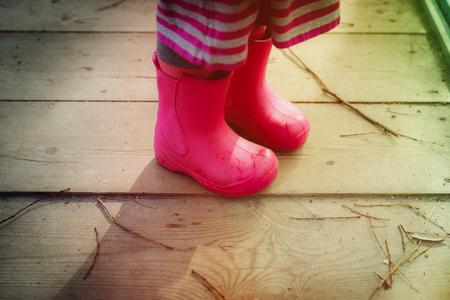 little girl in rainboots in autumn nature