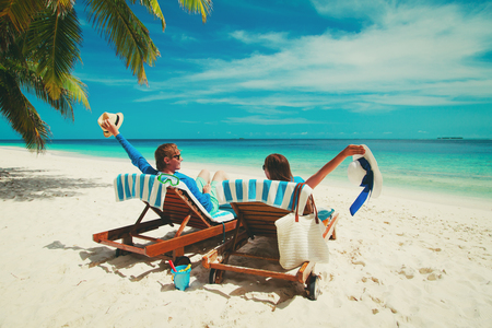 chairs: happy couple relax on a tropical beach