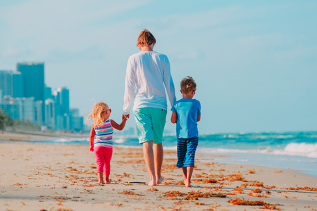 father and two kids walking on beach