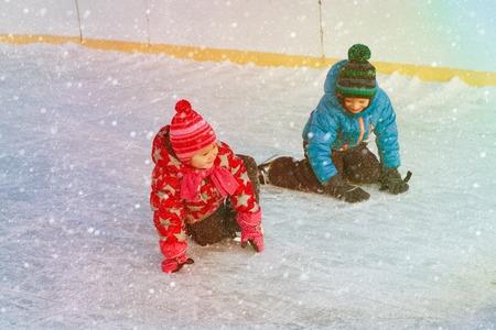 little boy and girl learning to skate, kids winter sport Banco de Imagens