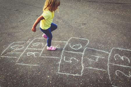 小さな女の子が遊び場で石蹴りを遊んで 写真素材