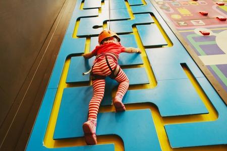little girl climbing wall in sport center