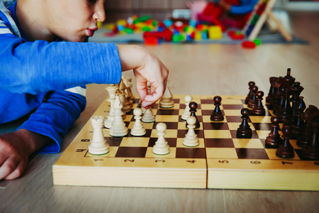 little boy learning to play chess in preschool