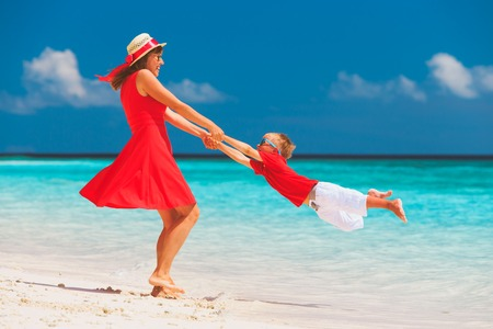 happy mother and little son play on beach