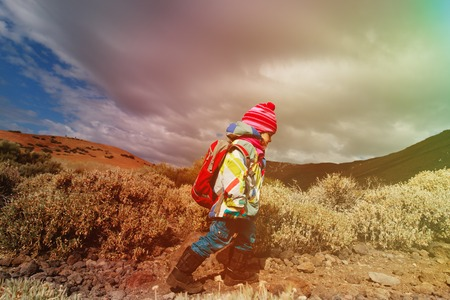 little girl with backpack hiking in mountains
