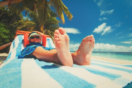 little boy relax on tropical beach, focus on feet