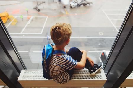 空港で飛行機旅行を見て少年