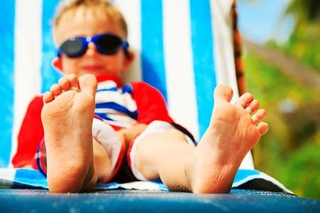 ragazzino rilassarsi sulla spiaggia tropicale, concentrarsi sui piedi