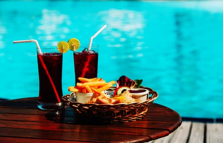 fish and chips with drinks served on tropical beach