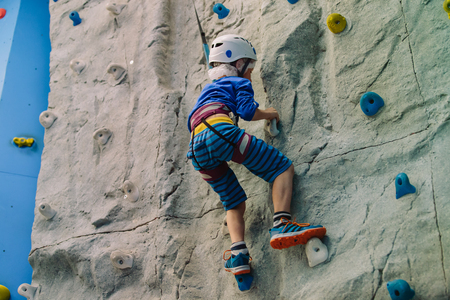 little boy climbing wall in sport center Stock Photo - 89460251