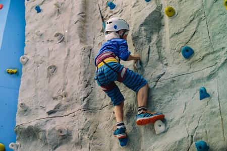 little boy climbing wall in sport center